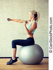 smiling woman with dumbbells and exercise ball - fitness,...