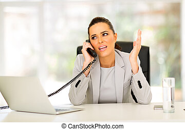 office worker talking on landline phone - confused office...