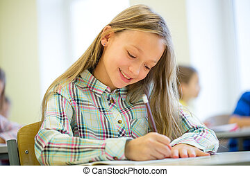 smiling school girl writing test in classroom - education,...