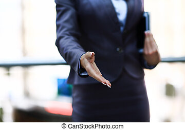 Businesswomans hand reaching out for handshake