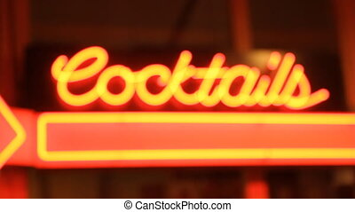Cocktails. - Neon Cocktails sign outside bar. Handheld with...