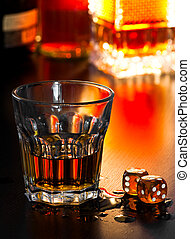 Gambling - Glass of whiskey with dice, shallow DOF