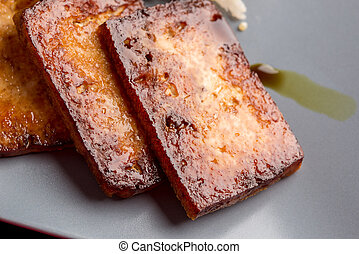 Closeup of backed marinated tofu with soy sauce on a blue...