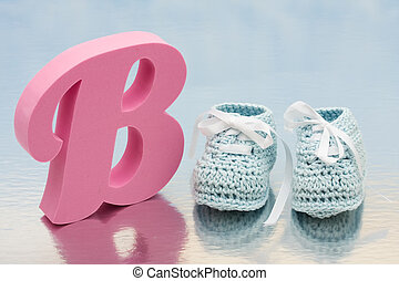 Baby Booties - Baby booties with a pink letter b on a shiny...