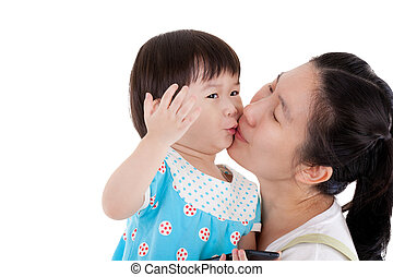 Asian mother carrying and smooching her daughter on white...