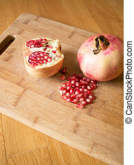 Cuted pomegranates with seeds on wooden board background