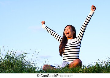 happy student outside - Happy woman student with arms lifted...