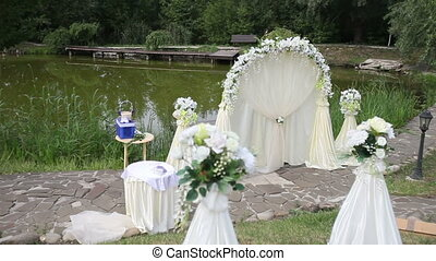 white arch for wedding on the lake near the trees and stone...
