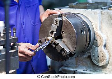 Milling machine operator working in factory workshop