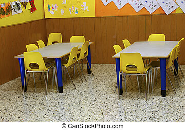 classroom of a preschool with the little yellow chairs -...