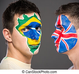 Face art. Flags. - Portrait of two men with painted flags on...