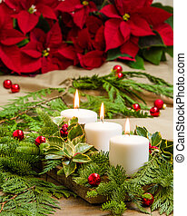 Lit candles with evergreens and poinsettias - Lit candles in...