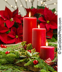 Lit candles on centerpiece with greens - Lit red candles in...