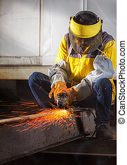 Worker hard work Electric wheel grinding on steel structure...