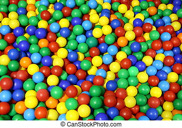 lots of blue green red yellow colored spheres into a pool of...