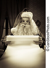 Santa with a long Christmas list - Santa Claus reading a...
