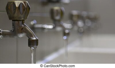 person closes many faucets to prevent water waste - man...