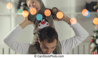 Happy father put his baby in the costume of a deer on the neck and playing with his little daughter