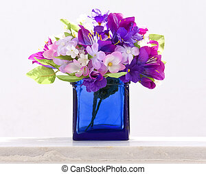 Decorative traditional blue bottle with fake flowers in it at Santorini island, Greece