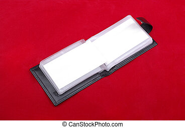 Opened black leather business card holder isolated on red background.