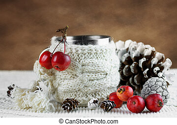 Cup in knitted cover with paradise apples and winter...