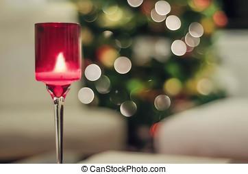 Vela de Navidad encendida, al fondo luces navidenas...