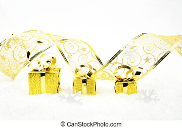 Golden christmas gifts with golden ribbon on snow -...