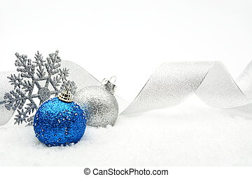Silver and blue christmas glittering baubles with ribbon on...