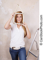 yardstick house shape - young woman made house shape from...