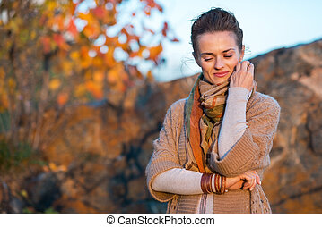 Portrait of young woman in autumn evening outdoors
