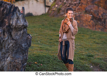 Happy young woman walking in autumn park in evening