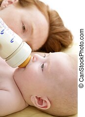 Mother feeding giving a milk bottle to her  baby