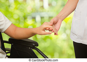 Doctor supporting patient in wheelchair on green background...