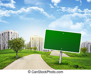 Blank green billboard and tree by road running through...