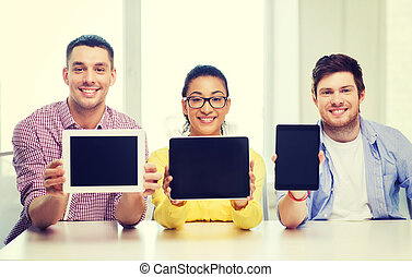smiling colleagues showing tablet pc blank screen -...