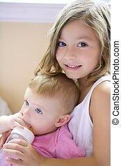 Toddler girl giving bottle of milk to baby sister - Toddler...