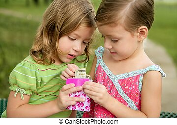 Two little twin girls find a dollar note inside a box - Two...