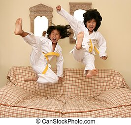 Two little asian judo girls jump on sofa - Two little asian...