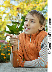 Little boy outdoors in autumn,shows on something