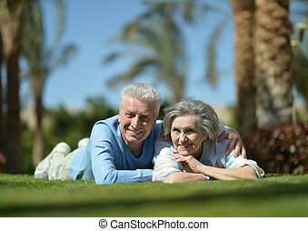 Happy elder couple resting on grass on nature
