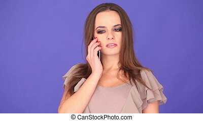 young woman on the phone - young brunette woman talking on...