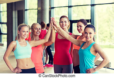 group of women making high five gesture in gym