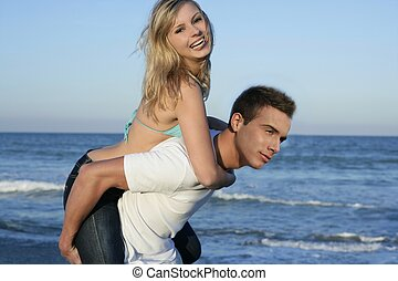 Young beautiful couple playing on the beach