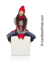 Winter woman sitting on big white box with copy space -...