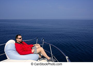 Man on bow boat relaxed on bean bag