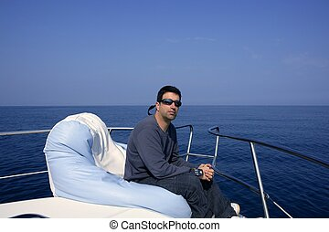 Man on bow boat relaxed on bean bag over blue sea