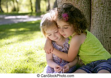 Two little sister girls hug playing under tree