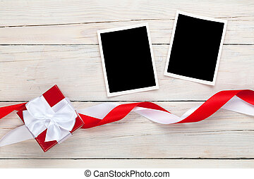 Photo frames and gift box with ribbons over white wooden...
