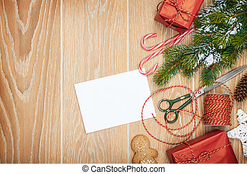 Christmas presents wrapping and snow fir tree over wooden...