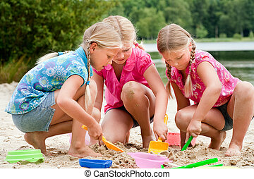 The girls digging in the sand - Happy children having fun in...